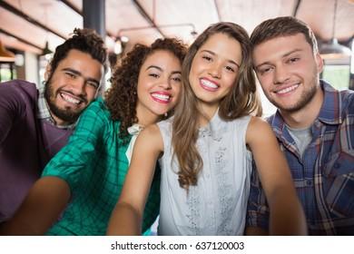 Portrait of cheerful friends in restaurant