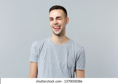 Portrait of cheerful funny blinking young man in casual clothes looking camera showing tongue isolated on grey wall background in studio. People sincere emotions lifestyle concept. Mock up copy space