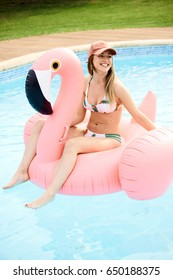 Portrait of cheerful girl in bikini and cap floating in pool on flamingo air mattress.