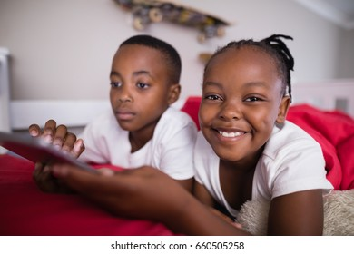 Portrait of cheerful girl with brother using mobile phone on bed at home