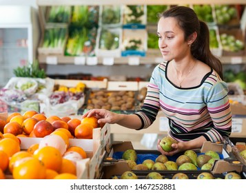 Portrait of cheerful girl choosing fruits at store