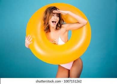 Portrait of a cheerful girl dressed in swimsuit looking through inflatable ring isolated over blue background