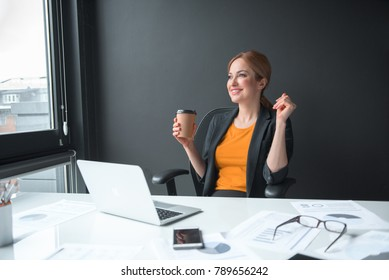 Portrait of cheerful girl drinking mug of coffee while sitting at table at work. Profession and break concept