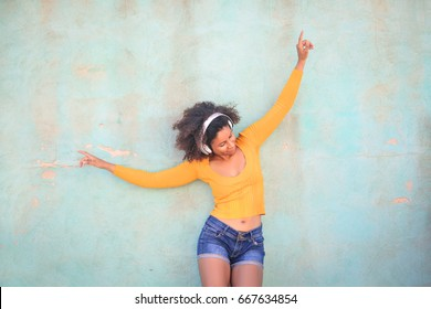 Portrait of a cheerful girl listening music and dancing