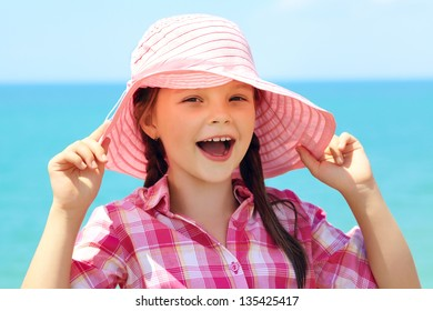 portrait of a cheerful girl in a pink hat on the background of the sea