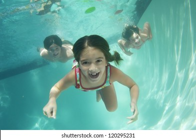 Portrait of a cheerful girl swimming underwater with friends in the background