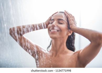 Portrait of cheerful girl taking shower. She touching head with hands