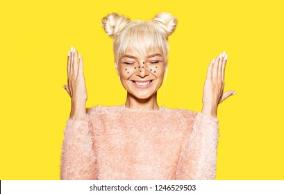Portrait of cheerful girl wearing festive glitter makeup. Blonde woman in trendy pink sweater. Positivity and emotions concept. Isolated on yellow background