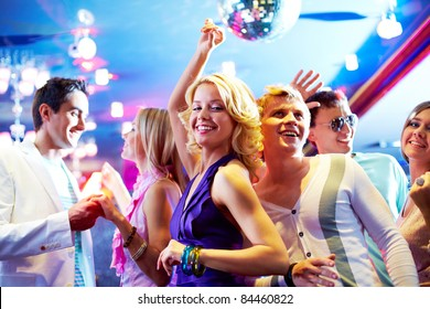 Portrait of cheerful girls and guys dancing at party