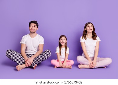 Portrait of cheerful glad family dad mom offspring daughter wearing cozy cotton pajama sitting on floor looking up idea copy space isolated on bright vivid shine vibrant violet color background