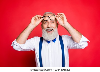 Portrait of cheerful, glad, old man raise his glasses on face, holding eyelet of spectacles with two hands, with wondered expression, open mouth, wearing blue bow-tie isolated on red background