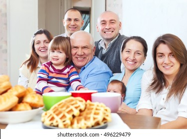 Portrait of cheerful grandparents with children and grandchildren in home interior together