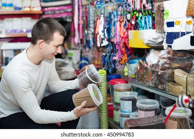 Portrait of cheerful guy selecting tasty treats in petshop