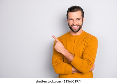 Portrait of cheerful handsome attractive bearded brutal fashionable modern stylish macho toothy beaming smile wearing tight sweater pointing on copy-space empty blank space isolated on gray background