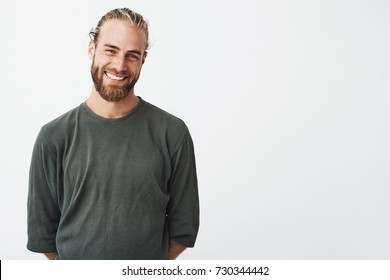 Portrait of cheerful handsome bearded guy with fashionable hairstyle smiling, posing for lookbook shoot for famous fashion brand.