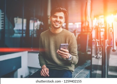Portrait of cheerful handsome male using mobile phone and wireless internet for chatting and networking , young hipster guy looking at camera satisfied with good 4G connection for sending messages