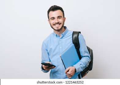 Portrait of cheerful handsome man holding laptop and phone over white background and looking at the camera.
