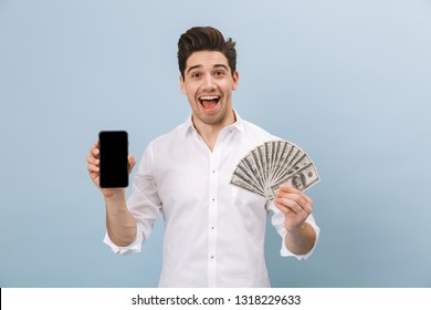 Portrait of a cheerful handsome young man standing isolated over blue background, showing money banknotes, showing blank screen mobile phone