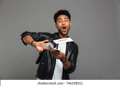 Portrait of a cheerful happy afro american man throwing money banknotes on camera isolated over gray background