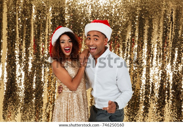Portrait of a cheerful happy afro american couple in red hats celebrating New Year while standing together and looking at camera isolated over golden shiny background