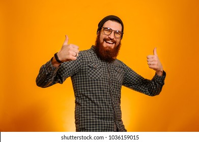 Portrait of cheerful happy bearded man wearing eyeglasses and hat and showing thumbs up over orange background, studio shot.