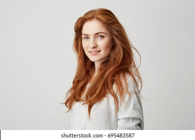 Portrait of cheerful happy beautiful girl with foxy hair smiling looking at camera over white background.