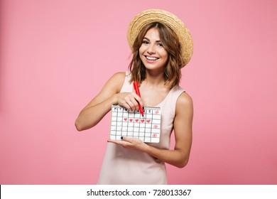 Portrait of a cheerful happy girl in summer hat checking her periods according to calendar with a felt-tip pen isolated over pink background