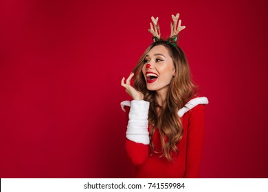 Portrait Of An Cheerful Happy Girl Wearing Christmas Deer Costume While Standing And Looking Away At