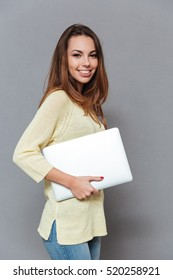Portrait of a cheerful happy gorl in sweater holding laptop isolated on the gray background