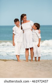 Portrait of a cheerful, happy mother and sons on beach, outdoor, Spain