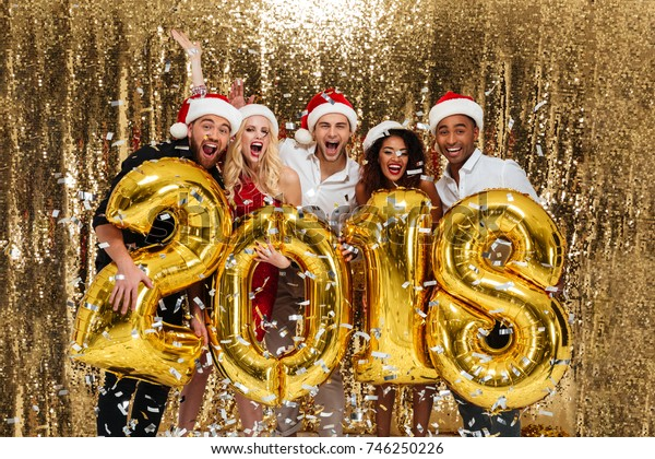 Portrait of a cheerful happy multhiethnic group of friends in red hats celebrating New Year while standing and holding air balloon golden 2018 numbers isolated over golden shiny background