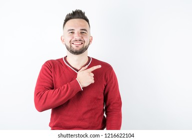 Portrait of cheerful happy young man pointing at upper right corner and smiling at camera
