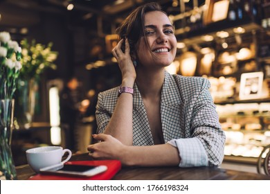Portrait of cheerful hipster girl 20 years old smiling at camera during pastime posing in coffee shop, successful female student in smart casual apparel feeling happiness at cafeteria table