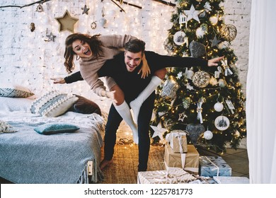 Portrait of cheerful hipster guy casual dressed looking at camera and laughing while joyful girlfrind having fun on his back, positive couple in Festive room with big Christmas tree and decorations