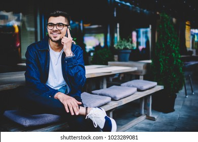 Portrait of cheerful hipster guy in spectacles talking on mobile with friend satisfied with tariffs for phone calls, smiling handsome young man looking at camera during conversation on smartphone