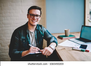 Portrait of cheerful hipster guy in spectacles enjoying studying in coworking space using wifi for online language course, prosperous male freelancer noting idea for publication working remotely