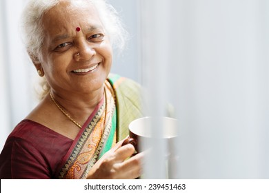 Portrait of cheerful Indian woman with a mug standing by the window
