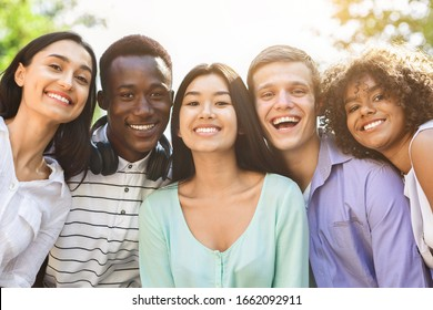 Portrait of cheerful interracial teen friends posing at camera outdoors, smiling and laughing, enjoying spending time together, closeup