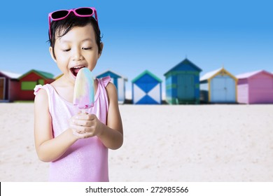 Portrait of cheerful kid standing on the shore while enjoy ice cream and wearing swimsuit