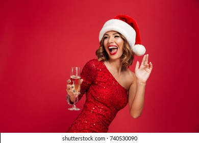 Portrait of a cheerful laughing woman in christmas hat and dress holding champagne glass while standing and looking away isolated over red background