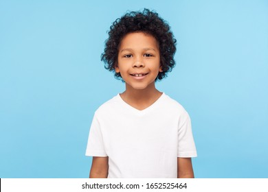 Portrait of cheerful little boy with curly hair in T-shirt smiling funny and carefree, showing two front teeth, healthy happy child, positive emotions. indoor studio shot isolated on blue background