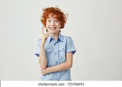 Portrait of cheerful little boy with ginger hair and freckles smiling, pointing upside with finger, having crazy expression. Copy space.