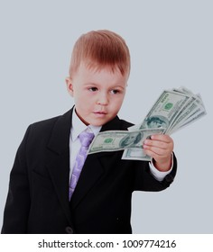 Portrait of a cheerful little boy holding a dollars over white background.