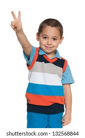 A portrait of a cheerful little boy shows victory sign on the white background
