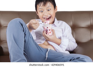 Portrait of a cheerful little boy sitting on the sofa while enjoying ice cream
