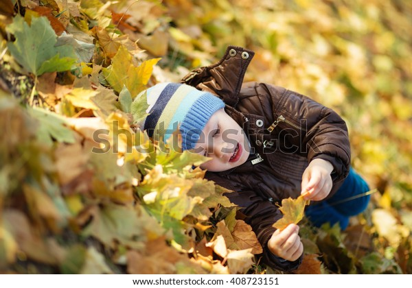 Portrait of a cheerful little boy wallow in fall foliage. Smiling funny little boy covered with autumn leaves. Little boy lying and having fun among multicolored autumn leaves in the park
