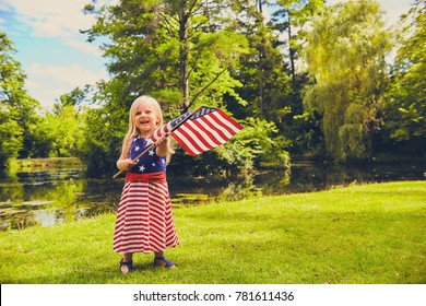 Portrait of cheerful little Caucasian girl wearing dress with stripes and starts waving USA flag in summer park