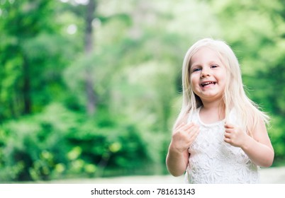 Portrait of cheerful little Caucasian girl wearing white dress looking at camera and smiling