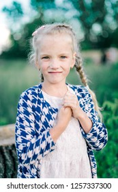 Portrait of a cheerful little girl with pigtails on summer background