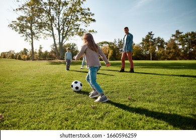 Portrait of cheerful little girl playing football with her family in the park on a sunny day. They are having fun while running. Family, kids, leisure and nature concept. Horizontal shot.